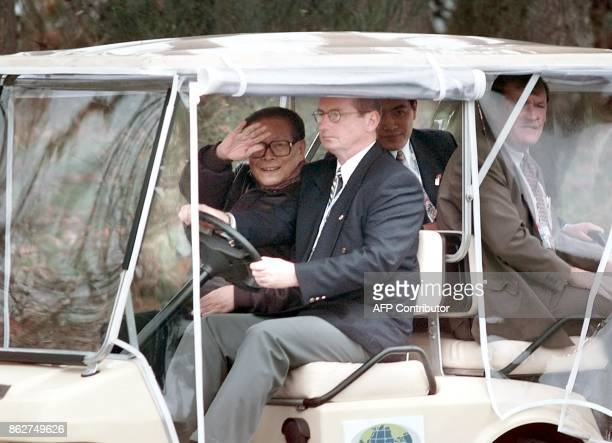Chinese President Jiang Zemin waves from a golf cart as he departs a group photo session with other leaders of the Asia Pacific Economic Cooperation...