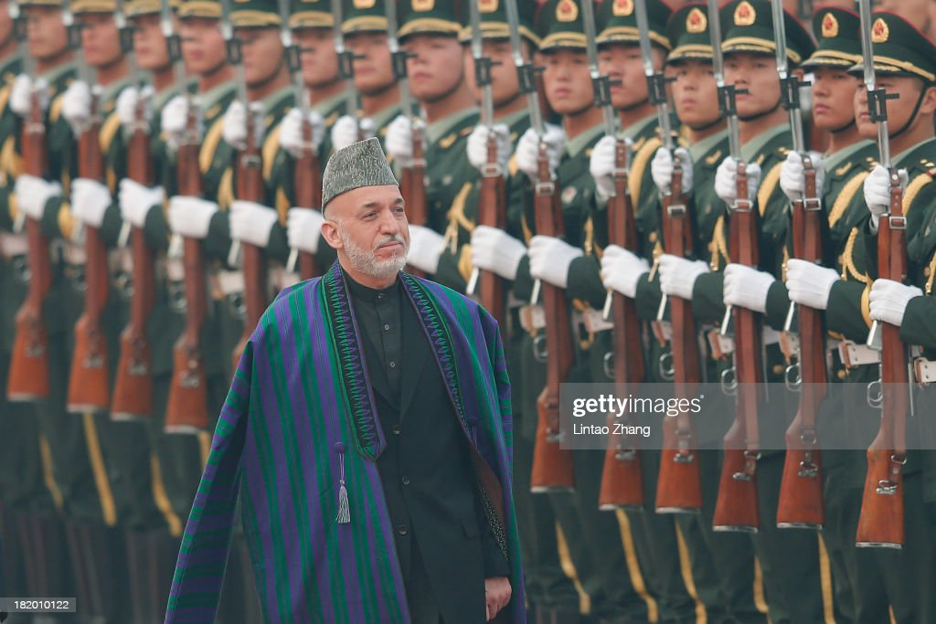 Chinese President Xi Jinpin accompanies Afghan President Hamid Karzai to view an honour guard during a welcoming ceremony outside the Great Hall of...