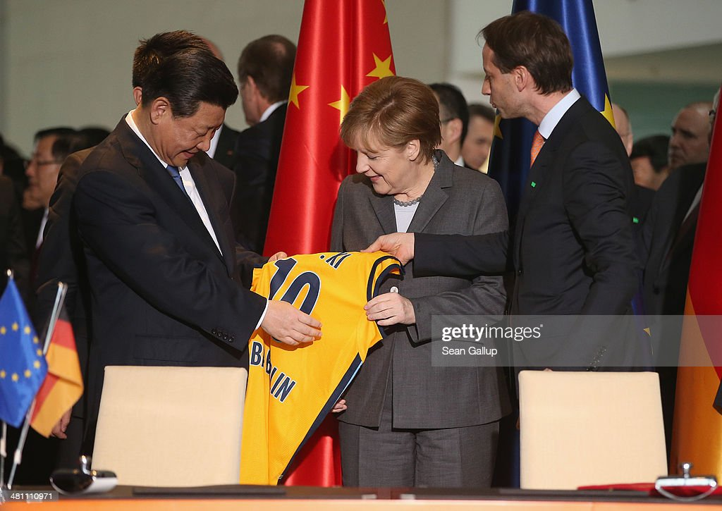 Chinese President <a gi-track='captionPersonalityLinkClicked' href=/galleries/search?phrase=Xi+Jinping&family=editorial&specificpeople=2598986 ng-click='$event.stopPropagation()'>Xi Jinping</a> accepts a jersey from the Alba Berlin basketball team with his name on it as German Chancellor <a gi-track='captionPersonalityLinkClicked' href=/galleries/search?phrase=Angela+Merkel&family=editorial&specificpeople=202161 ng-click='$event.stopPropagation()'>Angela Merkel</a> looks on during the signing of bilateral agreements at the Chancellery on March 28, 2014 in Berlin, Germany. President <a gi-track='captionPersonalityLinkClicked' href=/galleries/search?phrase=Xi+Jinping&family=editorial&specificpeople=2598986 ng-click='$event.stopPropagation()'>Xi Jinping</a> is on a two-day official visit to Germany.