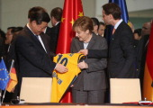Chinese President Xi Jinping accepts a jersey from the Alba Berlin basketball team with his name on it as German Chancellor Angela Merkel looks on...