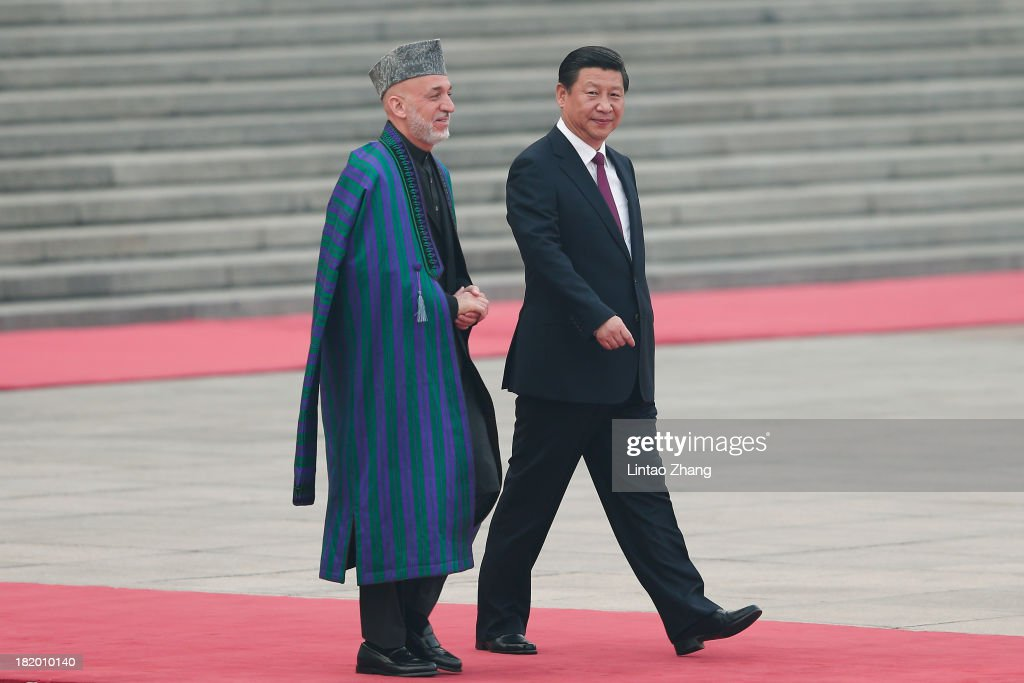 Chinese President Xi Jinping accompanies Afghan President Hamid Karzai to view an honour guard during a welcoming ceremony outside the Great Hall of...