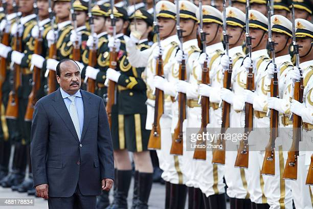 Chinese President Xi Jinping accompanies Mauritania's President Mohamed Ould Abdel Aziz to view an honour guard during a welcoming ceremony outside...