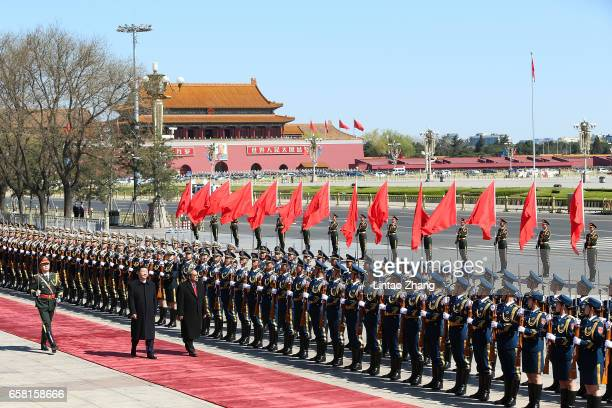 Chinese President Xi Jinping accompanies Micronesia's President Peter Christian to view a guard of honour during a welcoming ceremony outside the...