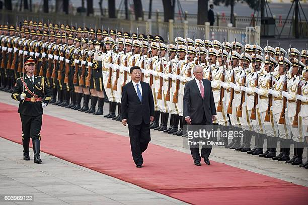 Chinese President Xi Jinping accompanies Peruvian President Pedro Pablo Kuczynski to view an honour guard during a welcoming ceremony outside the...