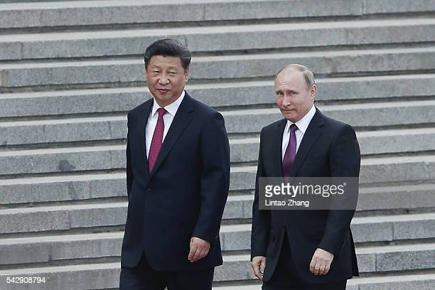 Chinese President Xi Jinping accompanies Russian President Vladimir Putin to view an honour guard during a welcoming ceremony outside the Great Hall...