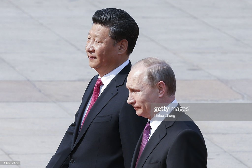 Chinese President Xi Jinping (L) accompanies Russian President Vladimir Putin (R) to view an honour guard during a welcoming ceremony outside the Great Hall of the People on June 25, 2016 in Beijing, China. Russian President Vladimir Putin is in China to discuss more economic and military cooperation between the two countries.