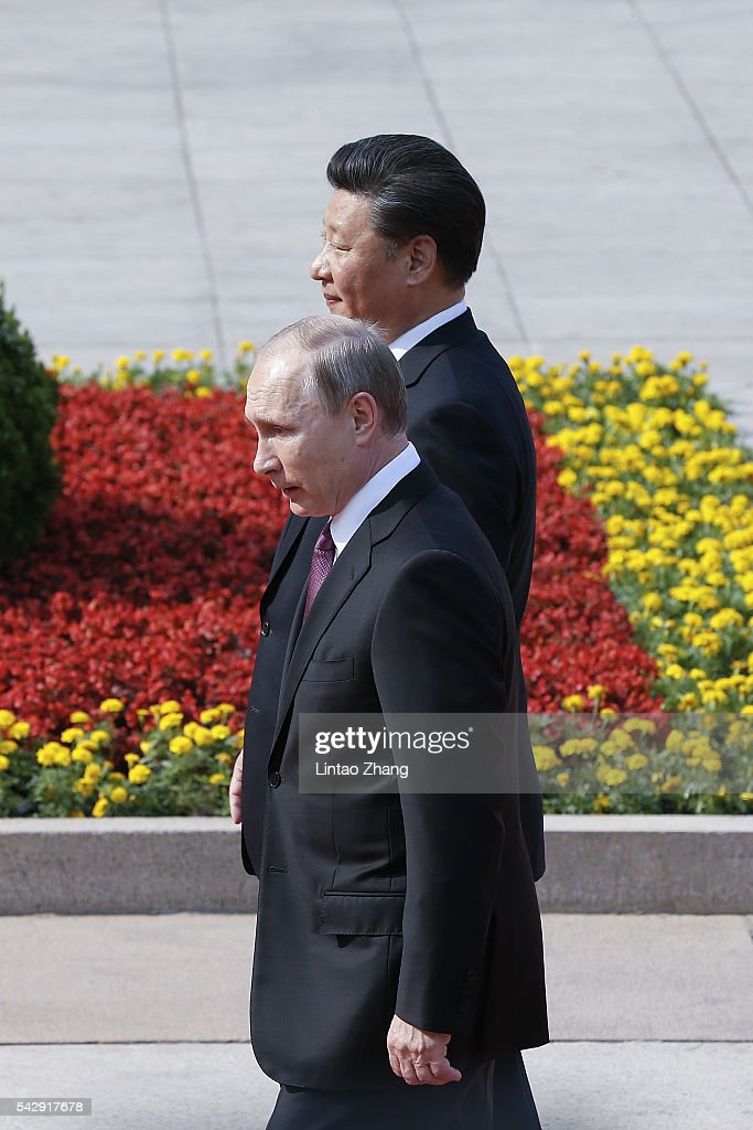 Chinese President Xi Jinping accompanies Russian President Vladimir Putin to view an honour guard during a welcoming ceremony outside the Great Hall of the People on June 25, 2016 in Beijing, China. Russian President Vladimir Putin is in China to discuss more economic and military cooperation between the two countries.