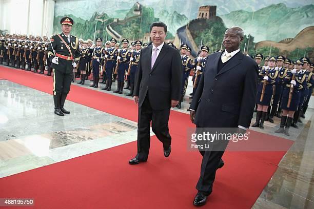 Chinese President Xi Jinping accompanies Ugandan President Yoweri Kaguta Museveni to view an honour guard during a welcoming ceremony inside the...