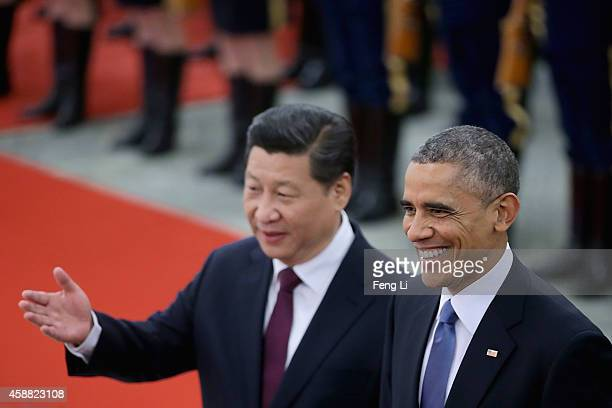 Chinese President Xi Jinping accompanies US President Barack Obama to view an honour guard during a welcoming ceremony outside the Great Hall of the...