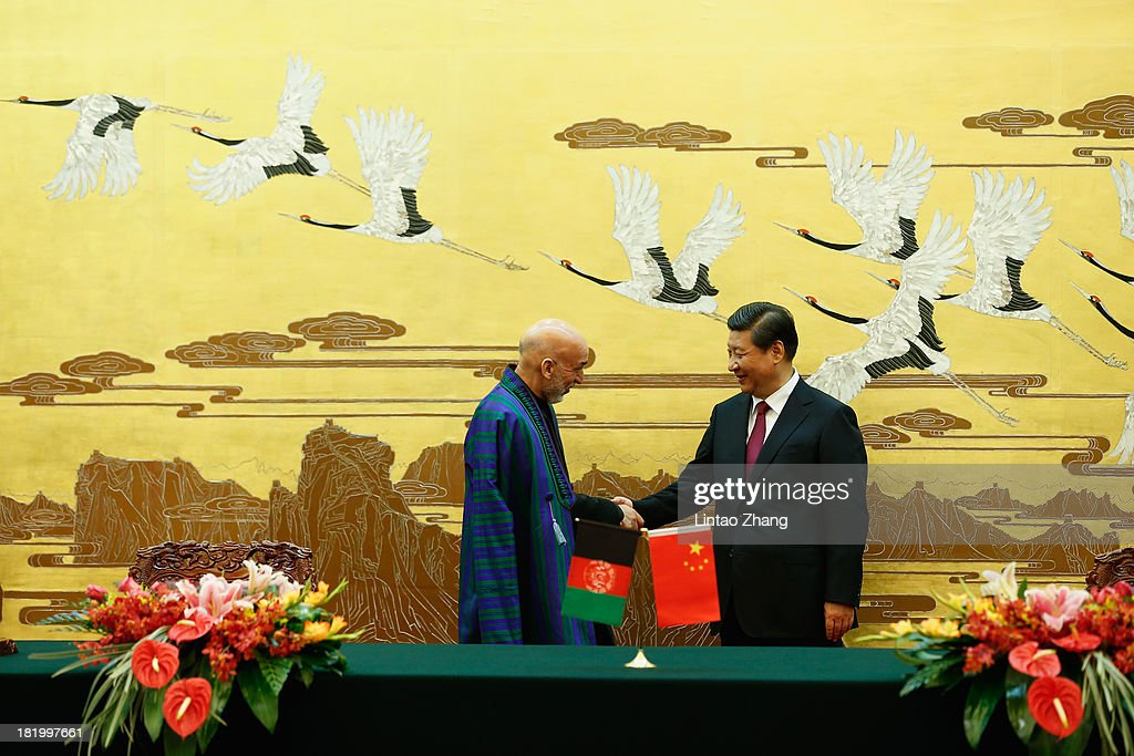 Chinese President Xi Jinping and Afghan President Hamid Karzai attend the signing ceremony at the Great Hall of the People on September 27 2013 in...
