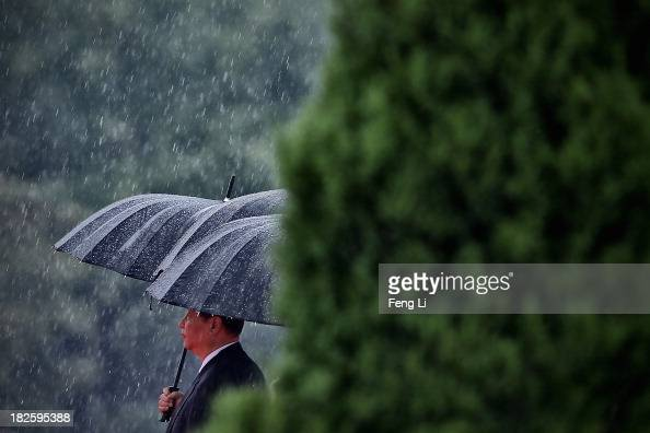 Chinese President Xi Jinping and Chinese Communist Party top leaders hold their umbrellas in the rain as they walk to the Monument to the People's...