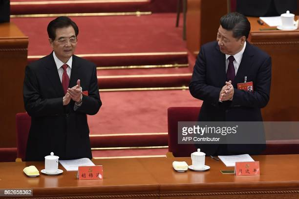 Chinese President Xi Jinping and Chinese former president Hu Jintao applaud at the opening session of the Chinese Communist Party's Congress at the...