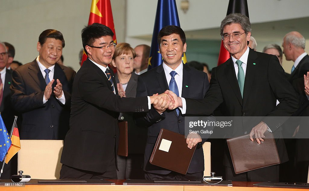 Chinese President Xi Jinping (L) and German Chancellor Angela Merkel (3rd from L) look on as Siemens AG CEO Joe Kaeser (R) shakes hands with Huang Dinan, Vice-Chairman of Shanghai Electric Group Co., Ltd. and Cao Peixi, Chairman of Huaneng Power International Inc. during the signing of bilateral agreements at the Chancellery on March 28, 2014 in Berlin, Germany. President Xi Jinping is on a two-day official visit to Germany.