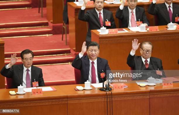 Chinese President Xi Jinping and his two immediate predecessors Hu Jintao and Jiang Zemin raise their hands during the closing ceremony of the...