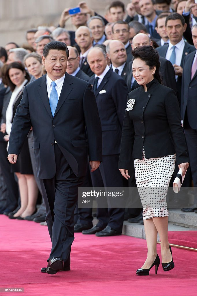 Chinese President Xi Jinping (L) and his wife Peng Liyuan (R) arrive on April 25, 2013 to take part in a welcoming ceremony for French President Francois Hollande at the Great Hall of the People in Beijing. Hollande is on a two-day visit to China, becaming the first Western leader to pay court to Beijing's new supremo.