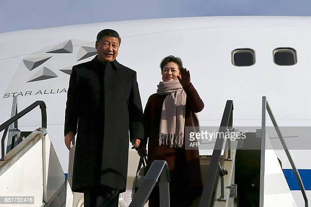 Chinese President Xi Jinping and his wife Peng Liyuan gesture and smile as they come out of the plane upon their arrival for a state visit to...