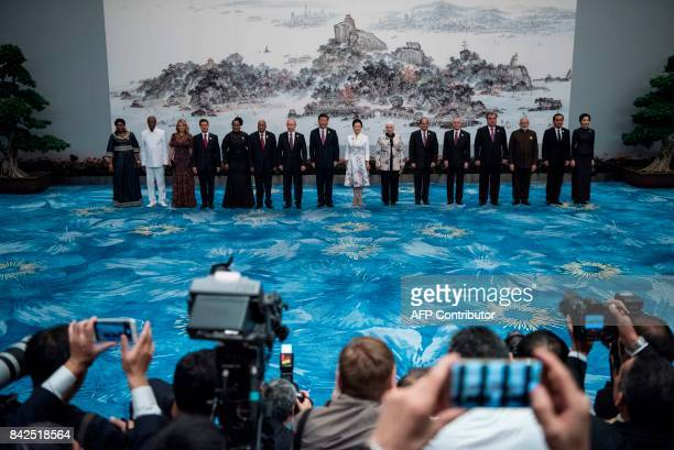 TOPSHOT Chinese President Xi Jinping and his wife Peng Liyuan pose with BRICS leaders and other invited heads of state and their spouses for a family...
