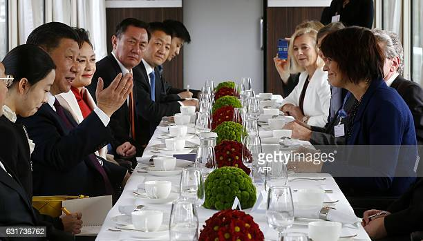 Chinese President Xi Jinping and his wife Peng Liyuan sit together with Swiss President Doris Leuthard in a train on their way to Bern during a state...
