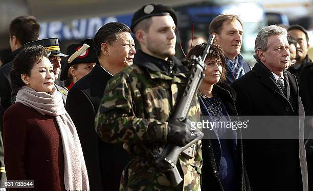 Chinese President Xi Jinping and his wife Peng Liyuan Swiss President Doris Leuthard and her husband Roland Hausin listen to the national anthems...
