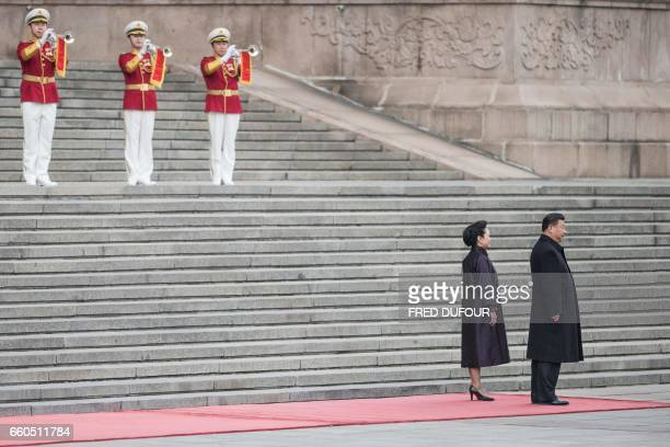 TOPSHOT Chinese President Xi Jinping and his wife Peng Liyuan wait for Serbian President Tomislav Nikolic during a welcome ceremony at the Great Hall...