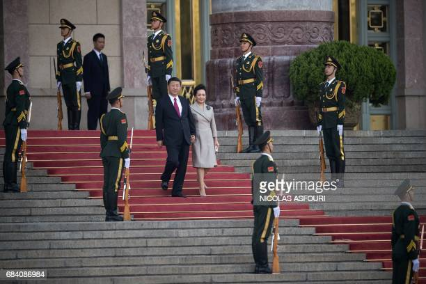 Chinese President Xi Jinping and his wife Peng Liyuan walk down stairs during a welcome ceremony for Argentine President Mauricio Macri outside the...