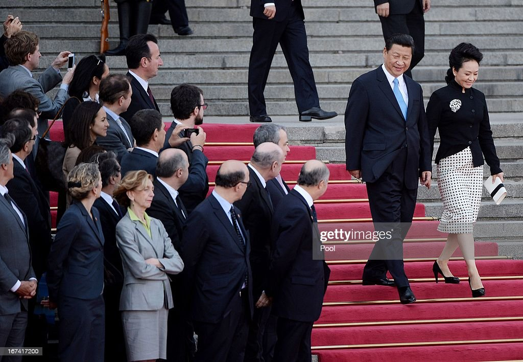 Chinese President Xi Jinping and his wife Peng Liyuan (R) walk past members of the French delegation as they arrive to greet French President Francois Hollande (not pictured) before reviewing an honour guard outside the Great Hall of the People in Beijing on April 25, 2013 in Beijing, China. Hollande has begun a two day trade visit to China bringing with him a large French trade delegation.