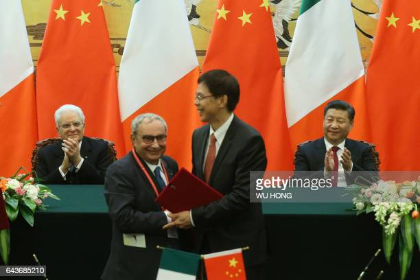 Chinese President Xi Jinping and Italian President Sergio Mattarella clap as officials from both countries sign documents to shake hands during a...