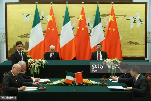 Chinese President Xi Jinping and Italian President Sergio Mattarella watch as officials from both countries sign documents during a signing ceremony...