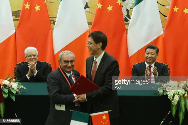 Chinese President Xi Jinping and Italian President Sergio Mattarella clap as officials from both countries sign documents and shake hands during a...