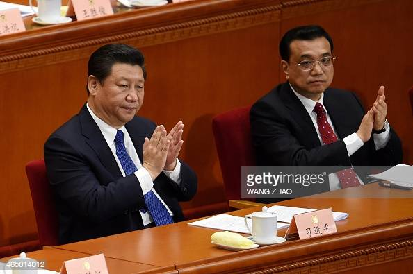 Chinese president Xi Jinping and premier Li Keqiang attend the opening session of the Chinese People's Political Consultative Conference applaud at...