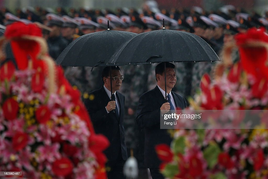Chinese President Xi Jinping (Right) and Premier Li Keqiang (Left) hold umbrellas as they arrive for a tribute ceremony marking the 64th anniversary of the founding of the People's Republic of China at Tiananmen Square on October 1, 2013 in Beijing, China. On October 1, 1949, Chinese leader Mao Zedong stood at the Tiananmen Rostrum to declare the founding of the People's Republic of China.