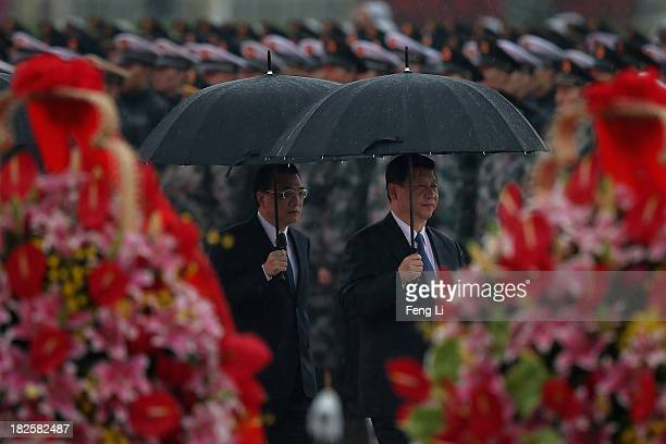 Chinese President Xi Jinping and Premier Li Keqiang hold umbrellas as they arrive for a tribute ceremony marking the 64th anniversary of the founding...
