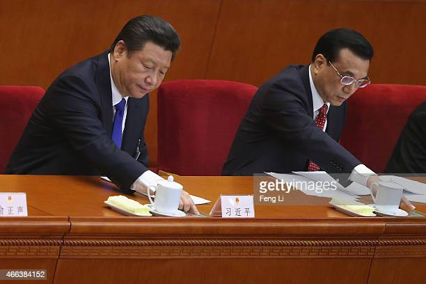 Chinese President Xi Jinping and Premier Li Keqiang press buttons to vote on the results of the work reports during the closing ceremony of China's...