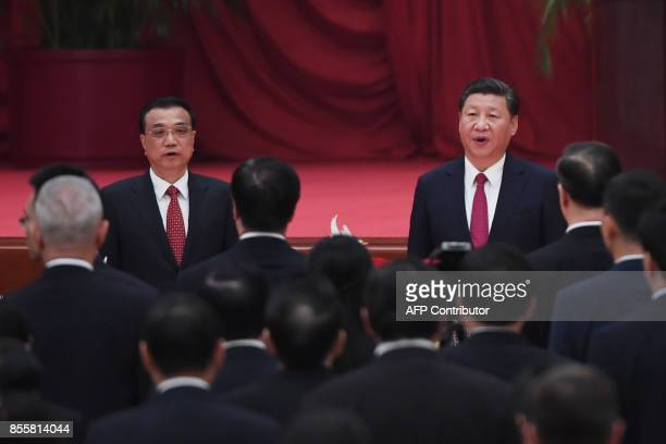 Chinese President Xi Jinping and Premier Li Keqiang sing the national anthem during a reception on the eve of China's National Day which marks the...