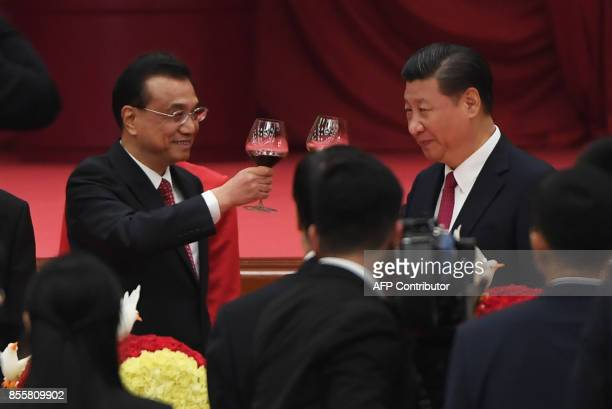 Chinese President Xi Jinping and Premier Li Keqiang toast during a reception on the eve of China's National Day which marks the 68th anniversary of...