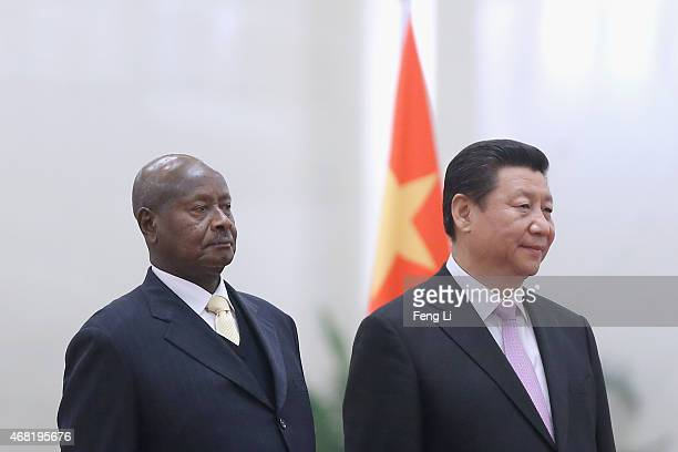 Chinese President Xi Jinping and Ugandan President Yoweri Kaguta Museveni listen to their national anthems during a welcoming ceremony inside the...