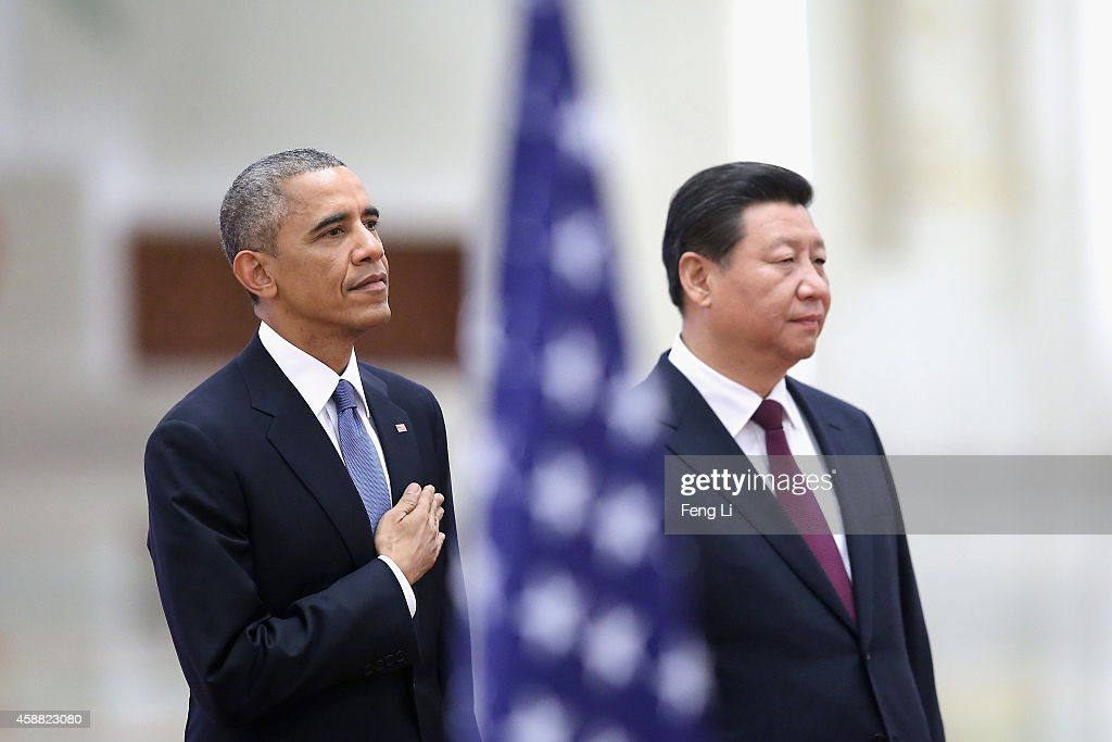 Chinese President Xi Jinping (R) and U.S. President Barack Obama (L) listen to their national anthems during a welcoming ceremony inside the Great Hall of the People on November 12, 2014 in Beijing, China. U.S. President Barack Obama pays a state visit to China after attending the 22nd Asia-Pacific Economic Cooperation (APEC) Economic Leaders' Meeting.