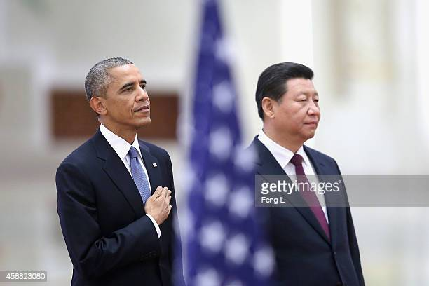 Chinese President Xi Jinping and US President Barack Obama listen to their national anthems during a welcoming ceremony inside the Great Hall of the...
