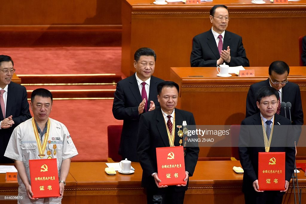 Chinese President Xi Jinping (C) applauds after honouring communist party members (front) duringThe Celebration Ceremony of the 95th Anniversary of the Founding of the Communist Party of China at the Great Hall of the People in Beijing on July 1, 2016. China's Communist Party take the ruling organisation's membership to almost 88 million and the anniversary of the Party's founding falls on July 1. / AFP / WANG