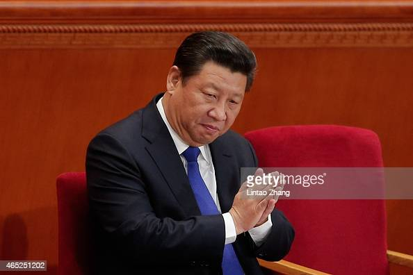 Chinese President Xi Jinping applauds during the opening of the 3rd Session of the 12th National People's Congress at the Great Hall of the People on...