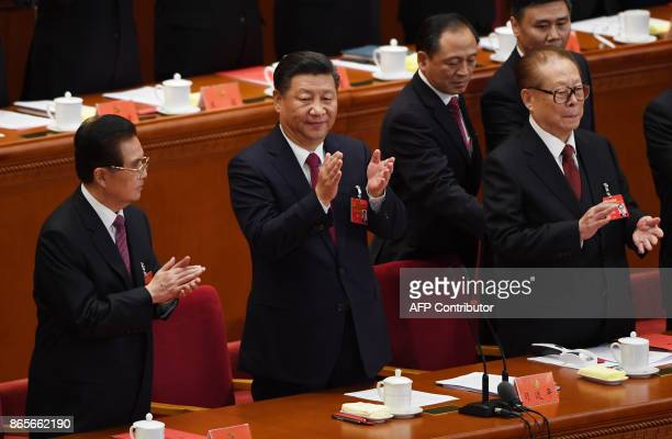 Chinese President Xi Jinping applauds with former presidents Hu Jintao and Jiang Zemin at the end of the closing session of the 19th Communist Party...