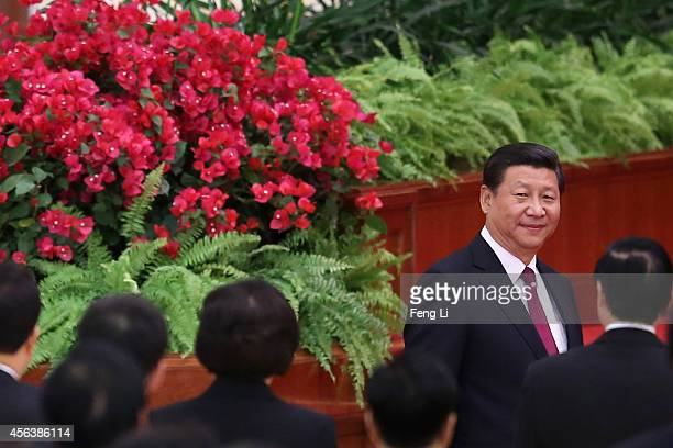 Chinese President Xi Jinping arrives for the National Day reception marking the 65th anniversary of the founding of the People's Republic of China at...