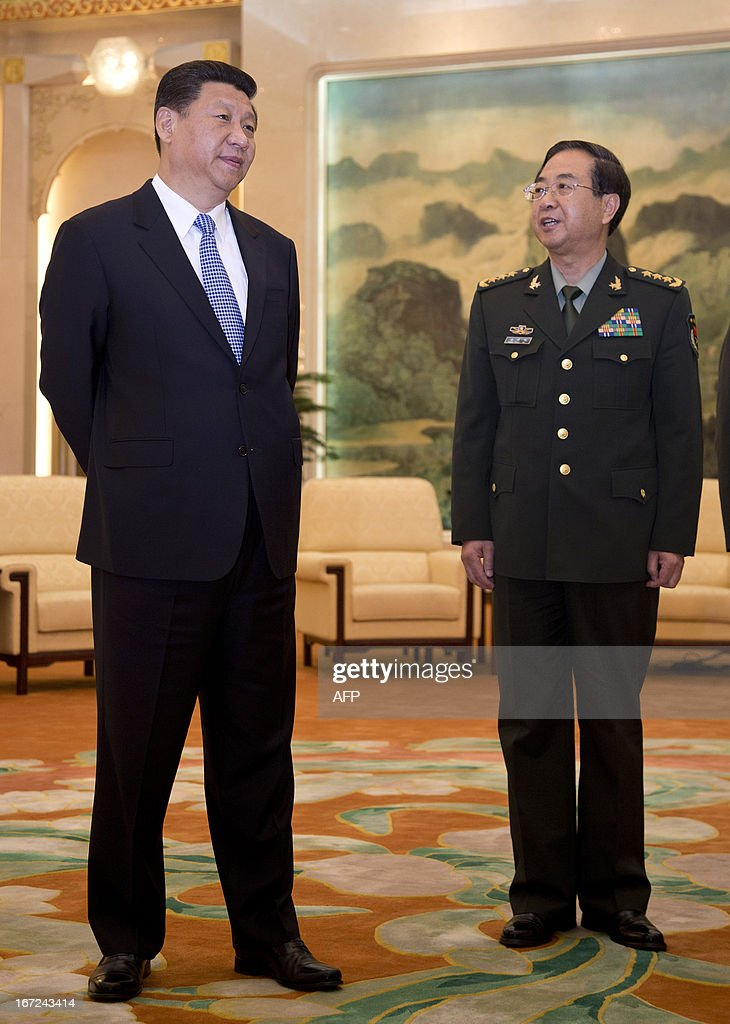 Chinese President Xi Jinping (L) chats to his Chief of the General Staff Gen. Fang Fenghui (R) while waiting for the arrival of US Joint Chiefs Chairman General Martin Dempsey at the Great Hall of the People in Beijing on April 23, 2013. Dempsey was expected to discuss concerns over tensions with North Korea, amongst other bilateral items. AFP PHOTO / POOL / Andy Wong