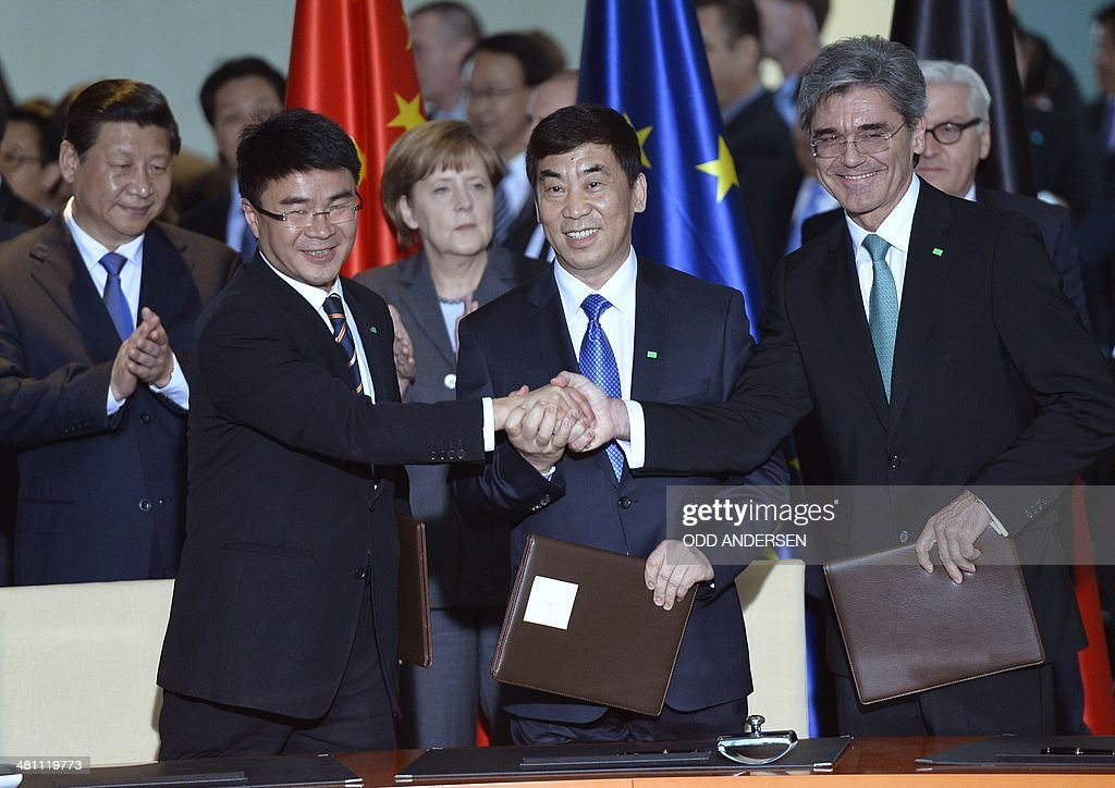 Chinese President Xi Jinping (L), German Chancellor Angela Merkel and German Foreign Minister Frank Walter Steinmeier look on as Siemens AG CEO Joe Kaeser (R), Vice-Chairman of Shanghai Electric Group Huang Dinan and Chairman of Huaneng Power International Cao Peixi shake hands after signing an agreement at the signature ceremony of political and economic agreements at the chancellery in Berlin on March 28, 2014. Chinese President Xi Jinping begins a landmark visit to fellow export powerhouse Germany, the third leg of his European tour, expected to cement flourishing trade ties and focus on the Crimea crisis.