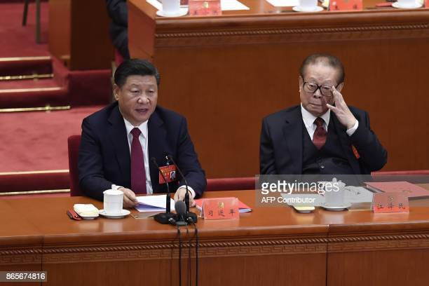 Chinese President Xi Jinping gives a speech as China's former president Jiang Zemin listens during the closing of the 19th Communist Party Congress...