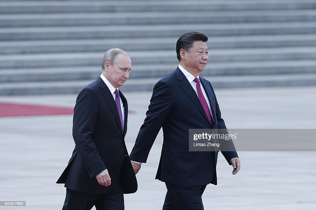 Chinese President Xi Jinping (R) invites Russian President Vladimir Putin (L) to view an honour guard during a welcoming ceremony outside the Great Hall of the People on June 25, 2016 in Beijing, China. Russian President Vladimir Putin is in China to discuss more economic and military cooperation between the two countries.