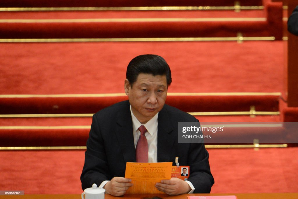Chinese President Xi Jinping looks on while reading his ballot papers prior to the election for the new president of China during the 12th National People's Congress (NPC) in the Great Hall of the People in Beijing on March 14, 2013. China's parliament is to name Xi Jinping as the country's new president on March 14, formalising his leadership of the world's most populous nation four months after he took charge of the ruling Communist Party.