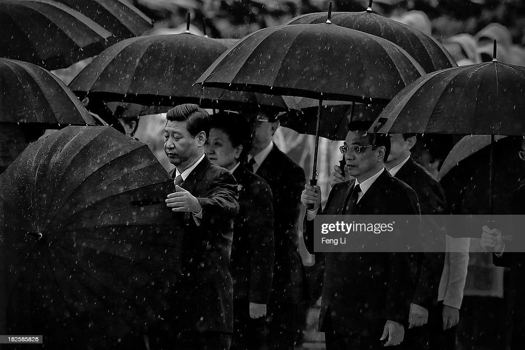 Chinese President Xi Jinping (Left) opens his umbrella as Premier Li Keqiang (Right) and Chinese Communist Party top leaders stand with umbrellas in the rain after bowing before the Monument to the People's Heroes during a ceremony marking the 64th anniversary of the founding of the People's Republic of China at Tiananmen Square on October 1, 2013 in Beijing, China. On October 1, 1949, Chinese leader Mao Zedong stood at the Tiananmen Rostrum to declare the founding of the People's Republic of China.