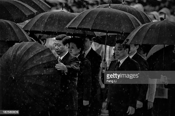 Chinese President Xi Jinping opens his umbrella as Premier Li Keqiang and Chinese Communist Party top leaders stand with umbrellas in the rain after...