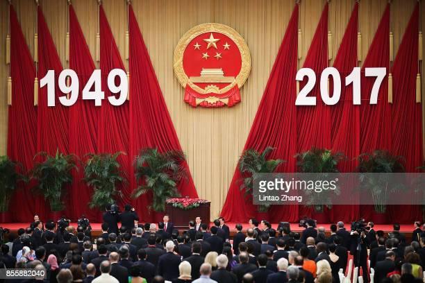 Chinese President Xi Jinping Premier Li Keqiang and National People's Congress Chairman Zhang Dejiang attend a reception marking the 64th anniversary...